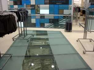 Glass and steel floor with old city wall visible beneath.