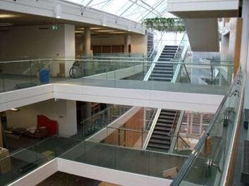 Stainless steel and glass bridges between floors in Atrium, with stairs in background.